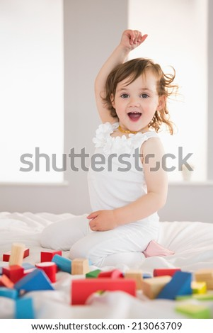 Portrait of a cute happy girl playing with building blocks on bed at home - stock photo