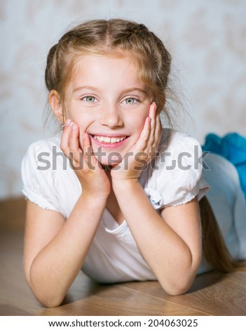 Portrait of a cute happy little girl laying on floor