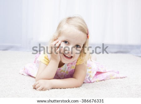 Portrait of a cute happy little girl laying on floor - stock photo