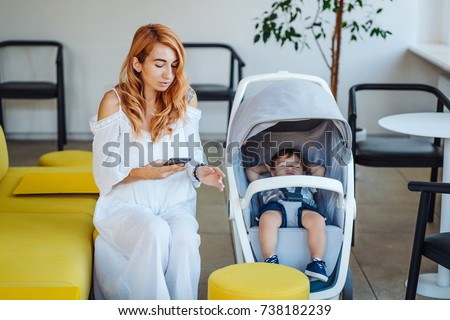Portrait of a cute happy mom and stroller with her baby