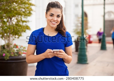 Portrait of a cute Hispanic female runner checking her cell phone before doing some exercise in the city - stock photo