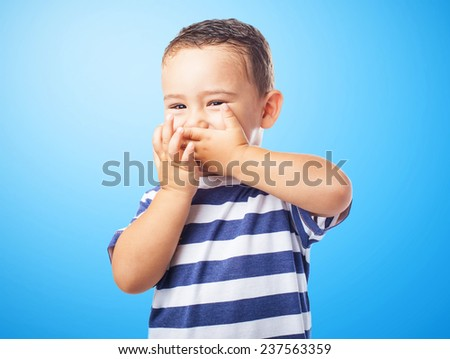 portrait of a cute kid covering his mouth with his hands - stock photo