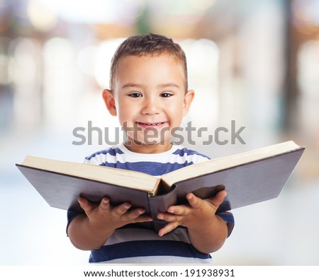 portrait of a cute kid holding a big book - stock photo