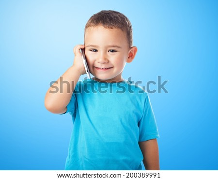 portrait of a cute kid talking on mobile phone - stock photo