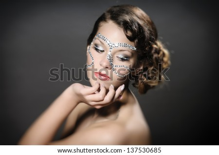 Portrait of a cute lady with diamonds and rhinestone-makeup.