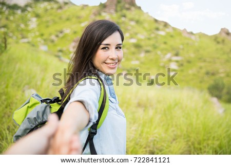 Portrait of a cute Latin woman holding her boyfriend by the hand while they stand on a beautiful mountain