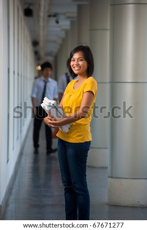 Portrait of a cute laughing college student in yellow t-shirt holding books on a modern university campus. Young female Asian Thai model late teens, early 20s of Chinese descent looking at camera