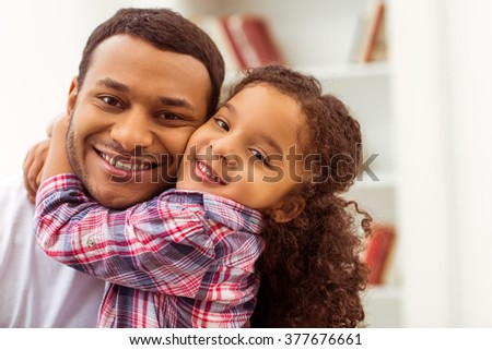 Portrait of a cute little Afro-American girl in casual clothes cuddling her handsome father. Both looking at camera and smiling. - stock photo