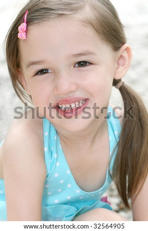 Portrait of a cute little Asian toddler girl in blue dress smiling