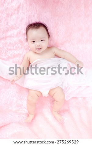 Portrait of a cute little baby on a pink fur bed - stock photo
