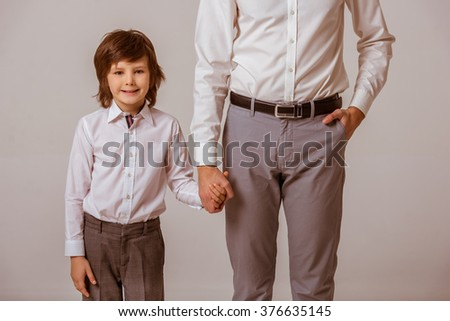 Portrait of a cute little boy and his father holding hands, looking in camera and smiling. Both in white classical shirts and gray pants, standing on a gray background, cropped - stock photo
