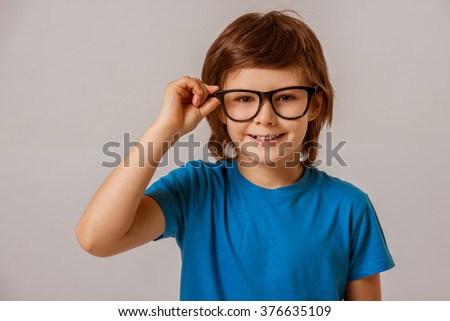 Portrait of a cute little boy in a blue t-shirt  and eyeglasses looking in camera and smiling while standing on a gray background - stock photo