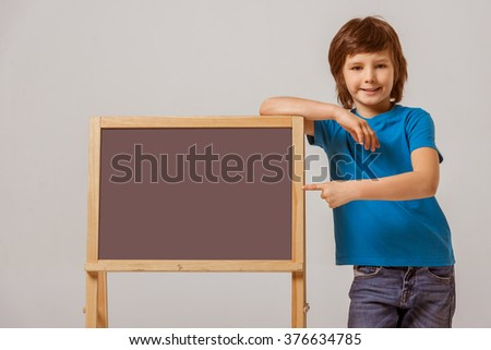 Portrait of a cute little boy in a blue t-shirt leaning on a blackboard and pointing on it, looking in camera and smiling while standing on a gray background - stock photo