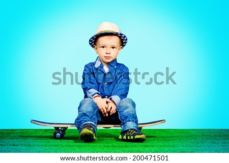 Portrait of a cute little boy in jeans clothes sitting on a skateboard. Fashion. Childhood. - stock photo