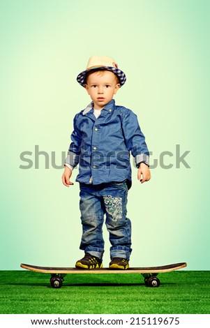 Portrait of a cute little boy in jeans clothes standing on a skateboard. Fashion. Childhood. - stock photo