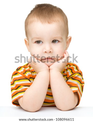 Portrait of a cute little boy looking at something while biting fingers, isolated over white