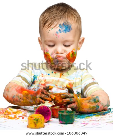 Portrait of a cute little boy messily playing with paints while making funny grimace, isolated over white - stock photo