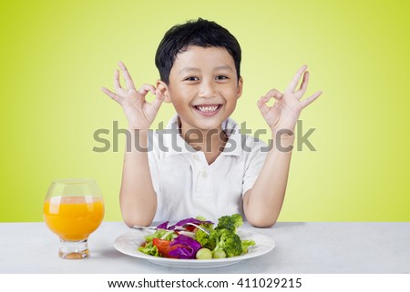 Portrait of a cute little boy showing OK sign with vegetables salad and orange juice on the table