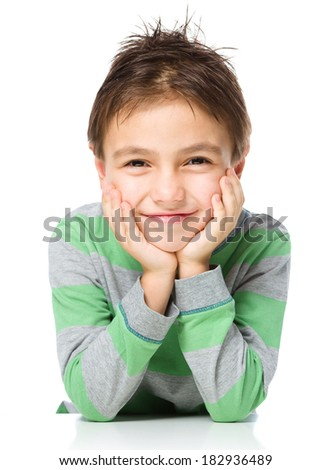 Portrait of a cute little boy sitting at table and supporting his head with hands, isolated over white - stock photo