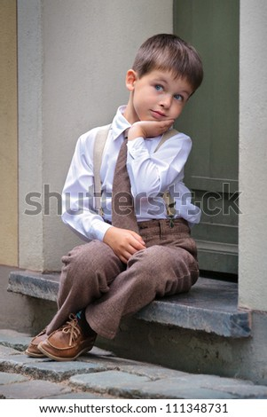 Portrait of a cute little boy sitting on the porch, facial expression series - stock photo