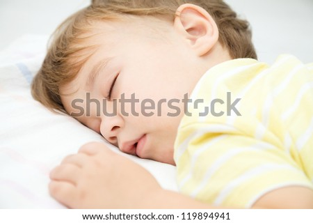 Portrait of a cute little boy sleeping on white pillow - stock photo