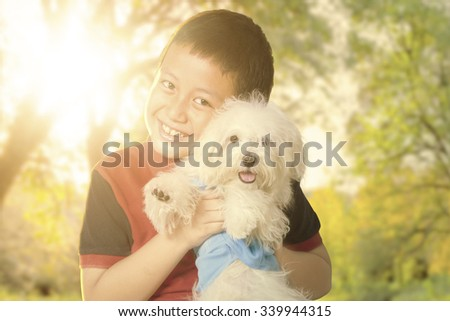 Portrait of a cute little boy smiling at the camera while hugging his puppy at the autumn park - stock photo