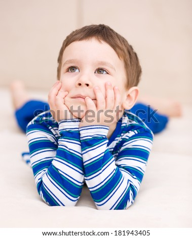 Portrait of a cute little boy supporting his head with hands - stock photo