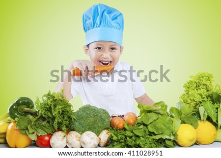 Portrait of a cute little boy wearing a cooking hat while eating a carrot and prepares vegetables - stock photo