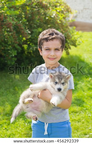 Portrait of a cute little boy with a husky puppy - stock photo