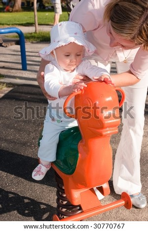 Portrait of a cute little caucasian baby girl and her mother having fun riding a spring horse