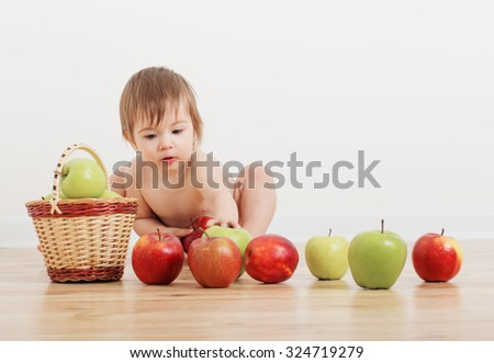 Portrait of a cute little child with apples indoor - stock photo