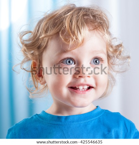Portrait of a cute little child with big blue eyes - stock photo