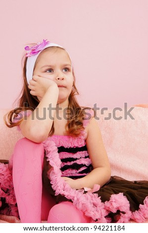 portrait of a cute little girl at couch - stock photo