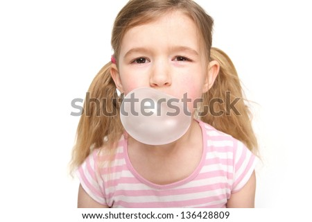 Portrait of a cute little girl blowing a bubble from chewing gum - stock photo