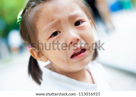 portrait of a cute little girl crying