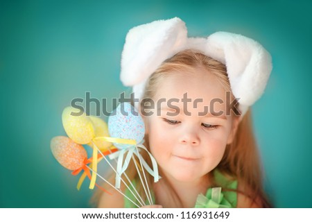 Portrait of a cute little girl dressed in Easter bunny ears holding colorful eggs - stock photo