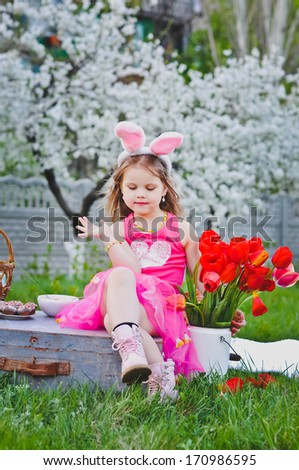 Portrait of a cute little girl dressed in Easter bunny ears outdoors - stock photo