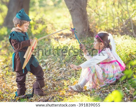 Portrait of a cute little girl dressed up as a fairy sitting in a magical forest and playing with a boy dressed up as a knight