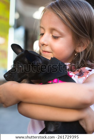 portrait of a cute little girl holding dog outdoors - stock photo