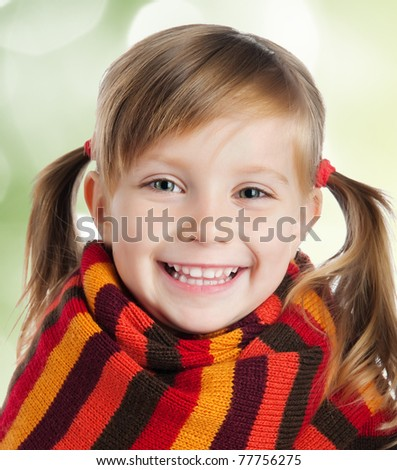 portrait of a cute little girl in a striped scarf - stock photo