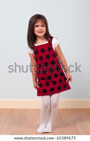 Portrait of a cute little girl in red dress indoors - stock photo