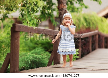 Portrait of a cute little girl in sunny summer day at green nature background - stock photo