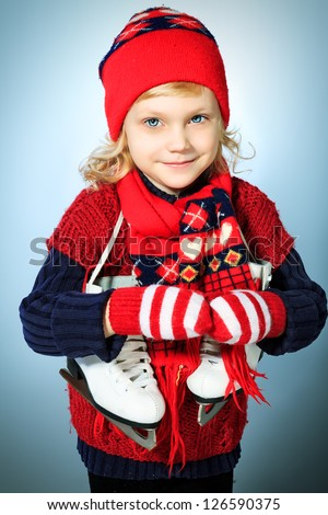 Portrait of a cute little girl in warm hat and sweater posing with figure skates. - stock photo