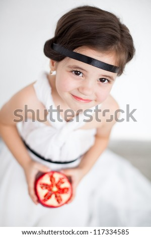 Portrait of a cute little girl model looks in luxurious white dress with makeup and hair decoration. Posing against a white wall with a pomegranate in her hand. - stock photo