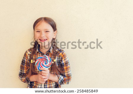 Portrait of a cute little girl of 7 years old, holding big colorful candy, wearing plaid shirt, toned image - stock photo