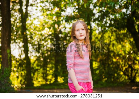 Portrait of a cute little girl of 7 years old in the park - stock photo