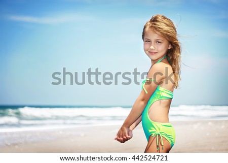 Portrait of a cute little girl on a beach, spending vacation in a summer camp on a seashore, happy healthy childhood - stock photo