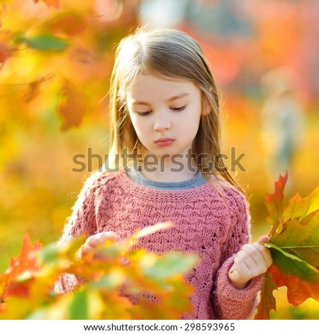 Portrait of a cute little girl on beautiful golden autumn day - stock photo