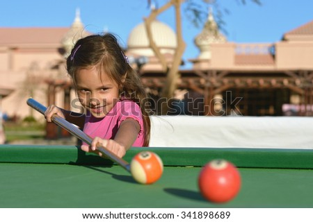 Portrait of a cute little girl playing billiards