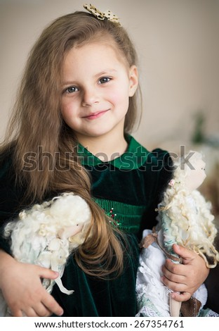 portrait of a cute little girl playing with her textile handmade princess dolls - stock photo